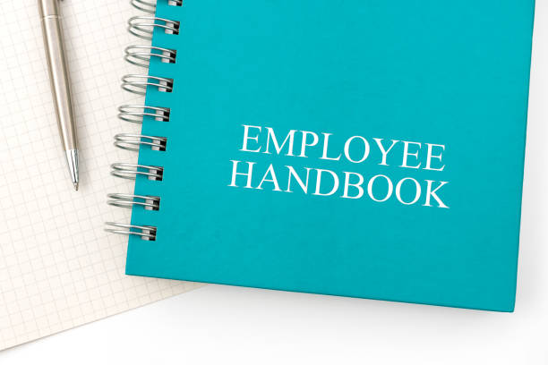 Employee Handbook or manual with a pen and paper on a white table in an office. Employee Handbook or manual with a pen and paper on a white table in an office - personnel management policy, explains business goals, results, defines personnel practices handbook stock pictures, royalty-free photos & images
