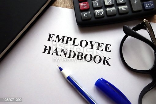 Employee handbook, pen, glasses and calculator on desk