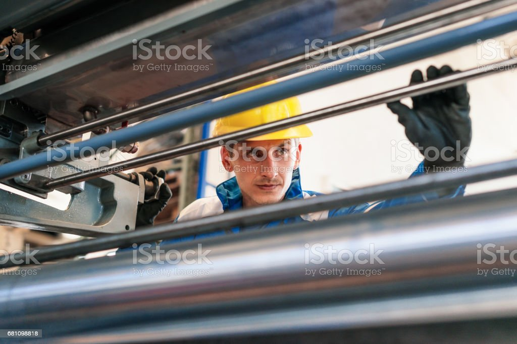 Employee in blue uniform working in factory - taking measures of roll bars royalty-free stock photo