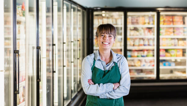 Employee in refrigerated section of supermarket stock photo