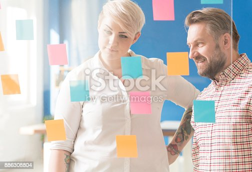 Employee looking at the sticky note covered glassboard with her supervisor