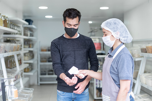Latin woman of average age of 25 years, dressed in a gray uniform and biosafety elements, an employee of a consumables business takes customers' temperatures when entering