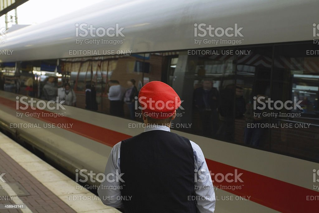 Employee of Deutsche Bahn and passing ICE stock photo