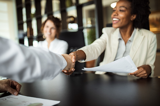 Business woman making plans with somebody, shaking hands.
