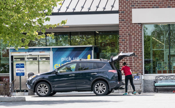 Employee Puts Groceries in Car Berks County, Pennsylvania, USA - May 19, 2020: Employee puts groceries in customers car at Weis Markets curb side pick-up. curbsidepickup stock pictures, royalty-free photos & images
