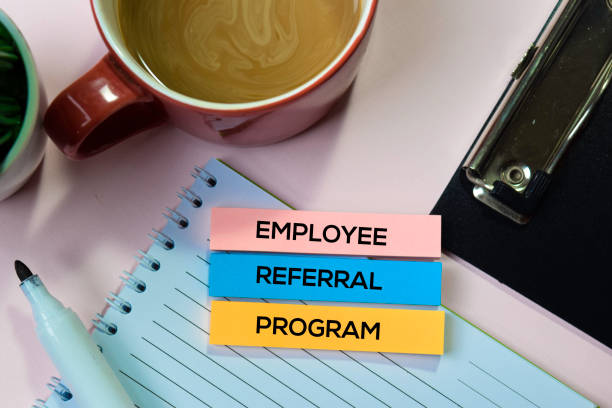 Employee Referral Program text on sticky notes with office desk concept stock photo