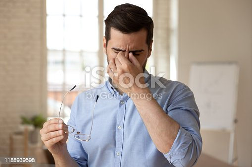 626964348istockphoto Employee suffering from dry eyes syndrome or eyestrain. 1188939598