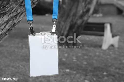 668954740istockphoto Employee tag hanging on a tree 668954778