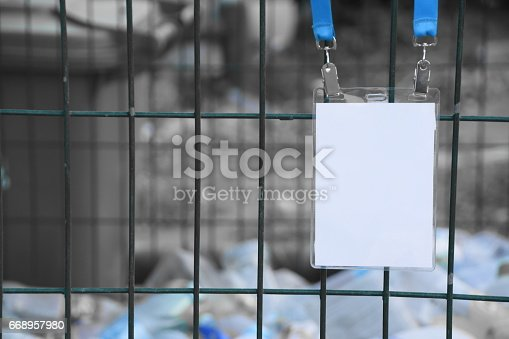 668954740istockphoto Employee tag hangs on a fence 668957980