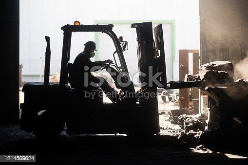 Employee using forklift in factory