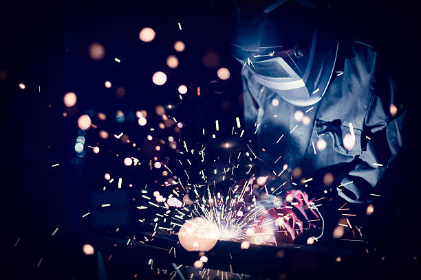 Employee welding steel Employee welding steel with sparks, using MiG MAG welder metalwork stock pictures, royalty-free photos & images