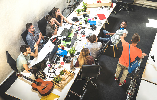 Employee Workers Group Having Fun At Urban Alternative Studio With Young Entrepreneur Coming In With Vintage Bike Business Concept Of Human Resource On Working Time Start Up Internship At Office Stock Photo - Download Image Now