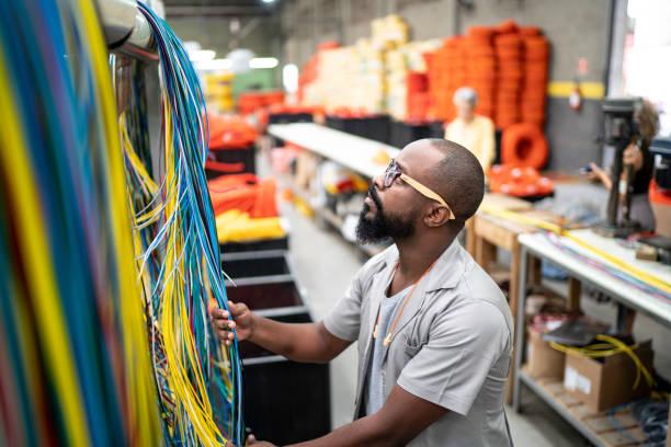 pracownik pracujący z przewodami w przemyśle - przewód składnik elektryczny zdjęcia i obrazy z banku zdjęć