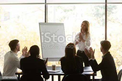 913332100 istock photo Employees applauding to woman speaker for successful flipchart presentation 1233105503