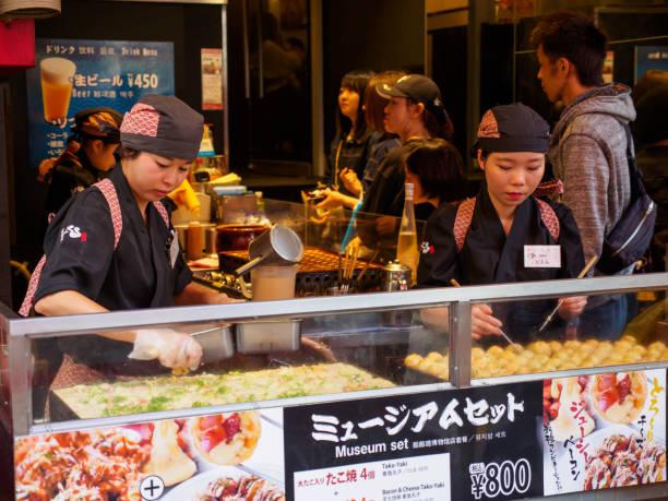 Employees cook Takoyaki, Osaka, Japan stock photo