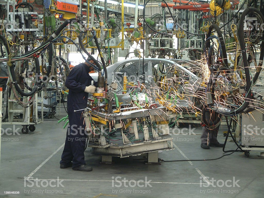 Employees diligently constructing new automobiles royalty-free stock photo