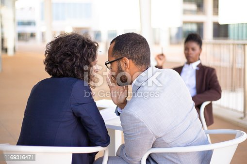 Employees gossiping about young female colleague. Business man and woman whispering, African American employee sitting in background. Office rumors concept