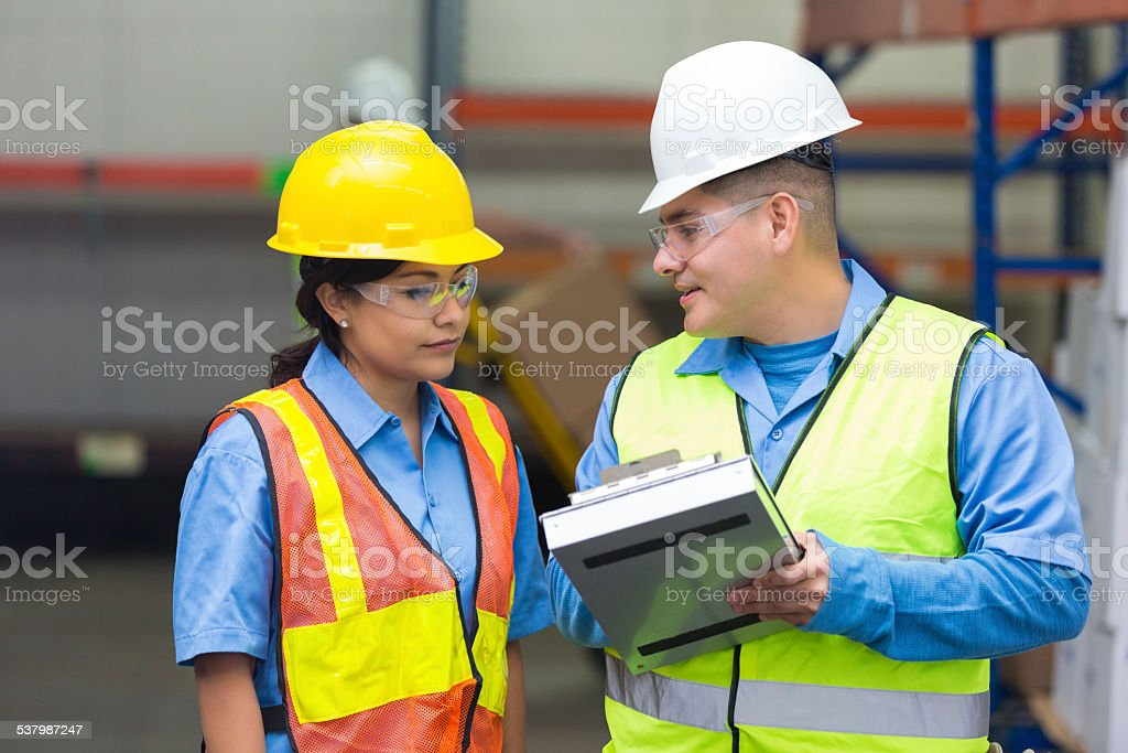 Employees in shipping distribution warehouse checking order on...