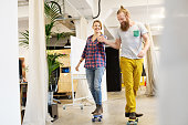 Young man and woman skating through the office and having fun
