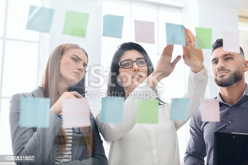 Employees sticking reminders on visualization board with business tasks and deadlines in office