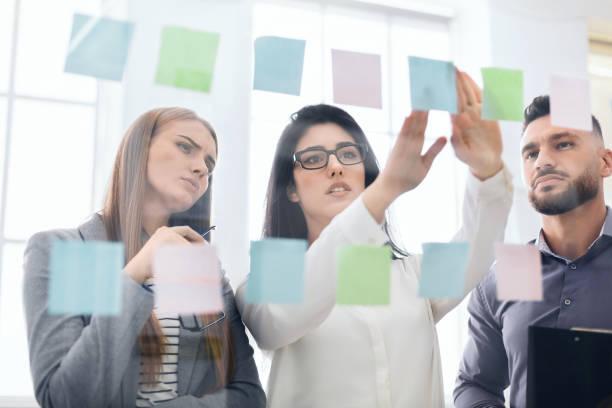 employees sticking reminders on visualization board in office - срочность стоковые фото и изображения
