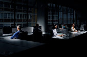 Team of employees using computers in dark office
