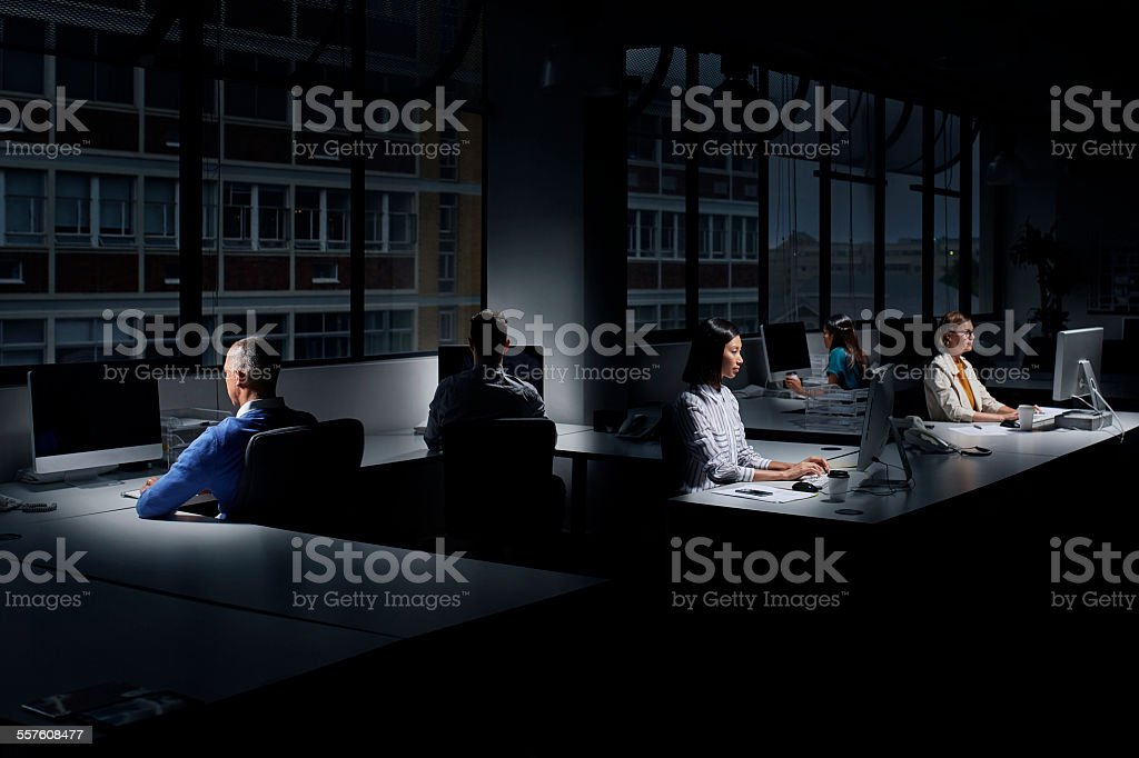 Employees using computers in dark office stock photo