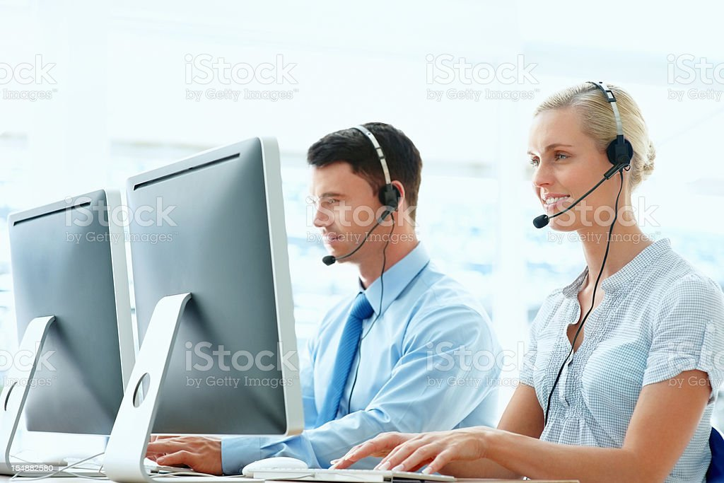 Employees wearing headsets and working in front of computer royalty-free stock photo