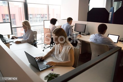 1124783373 istock photo Employees working in coworking office sitting at desk using computers 1127397424