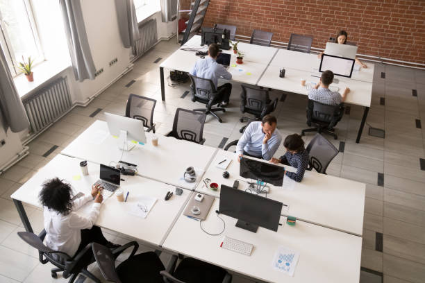 Employees working together in modern open office space stock photo