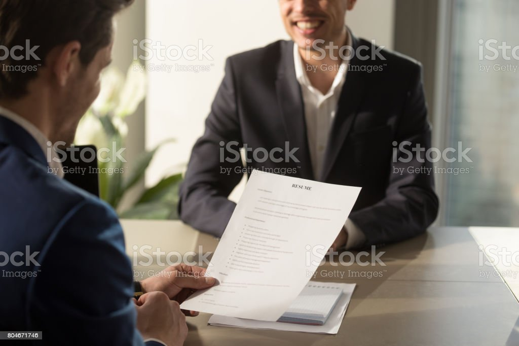 Employer conducting job interview, reviewing good resume of successful applicant stock photo