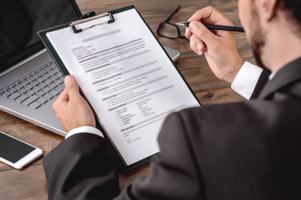 Employer filling candidate form sitting in office back view cllose-up stock photo