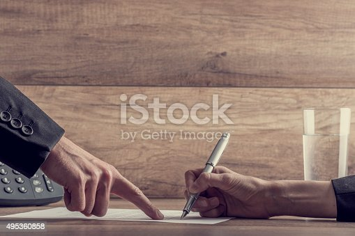 istock Employer showing his employee where to sign a contract 495360858