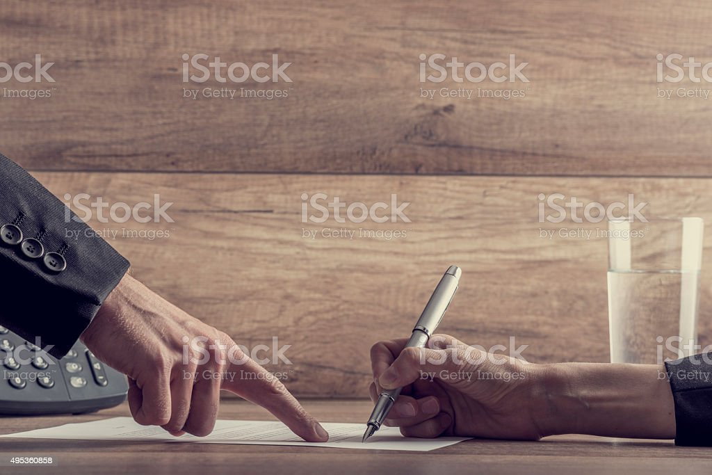 Employer showing his employee where to sign a contract stock photo