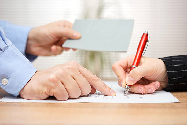 arbeitgeber zeigt mitarbeiter in zu unterzeichnen und damit ihre broschüre - kündigung arbeitsvertrag stock-fotos und bilder