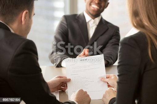 istock Employers recruiters reviewing resume, happy applicant at background, close up 695760164