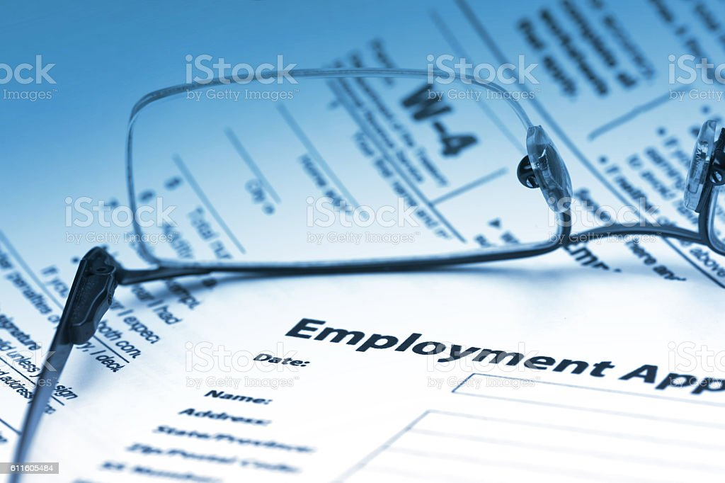 Employment agreement with W-4 form through reading glasses. stock photo