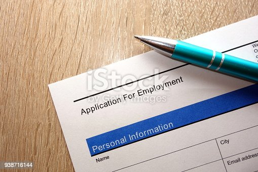 587228412istockphoto Employment application form and pen on desk 938716144