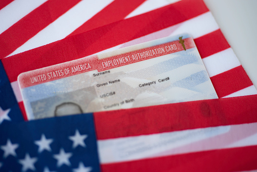Employment Authorization card on USA Flag surface. Close up view.