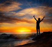 Empowered woman with arms raised at sunset.