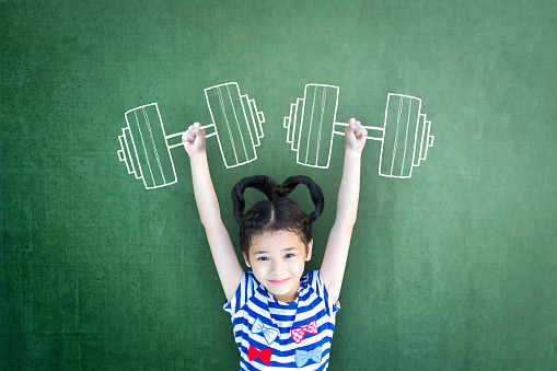 istock Empowering woman and girl gender rights concept for international day of girl child, and sports for development and peace with healthy strong kid with dumbbell exercise doodle on school chalkboard 956218378