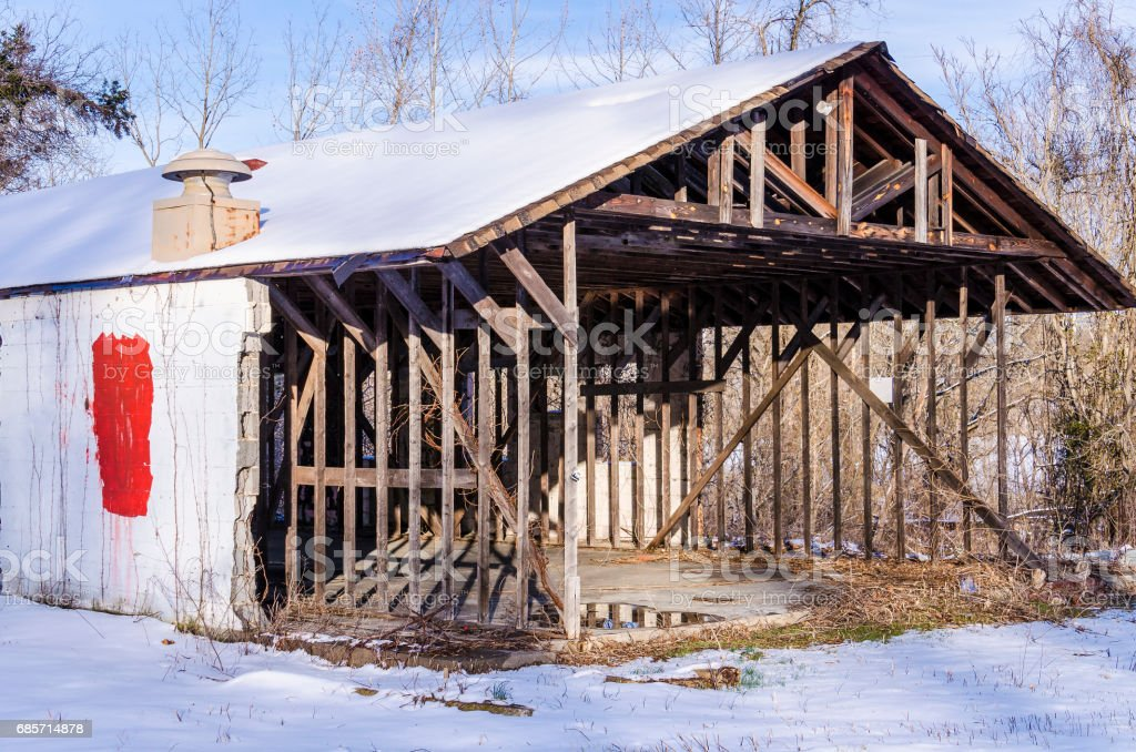 Empty abandoned barn stables during winter with snow in countryside on farm foto de stock royalty-free
