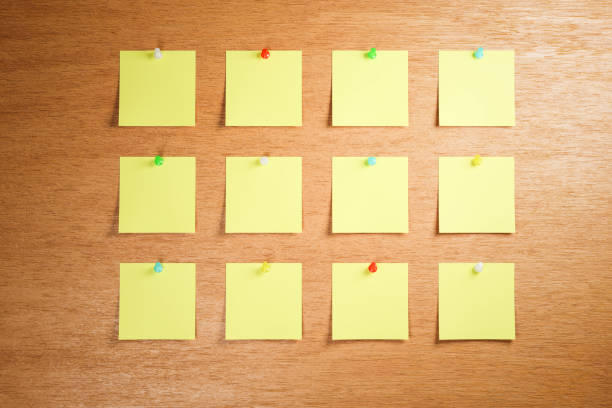 Empty adhesive notes attached to a wooden bulletin board. 3 rows with 4 pieces each. Differently colored thumbtacks / pins used. stock photo