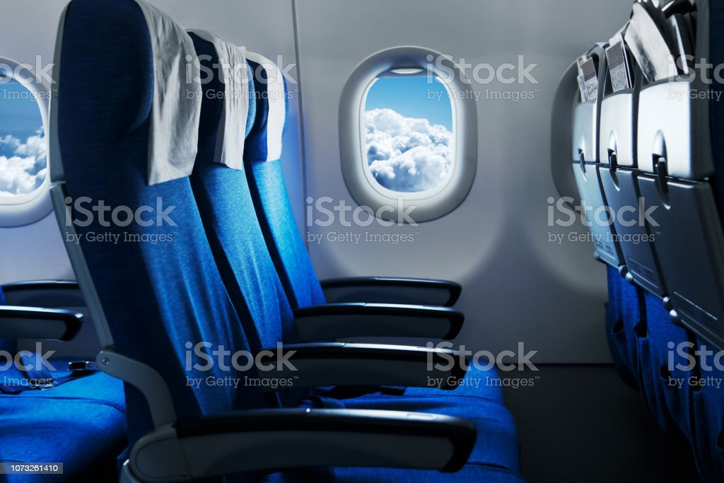 Empty air plane seats. Blue sky and clouds in the window. Airplane interior Empty air plane seats. Blue sky and clouds in the window. Airplane interior Air Vehicle Stock Photo