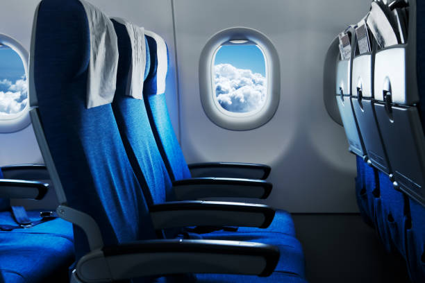 empty air plane seats. blue sky and clouds in the window. airplane interior - aereo di linea foto e immagini stock