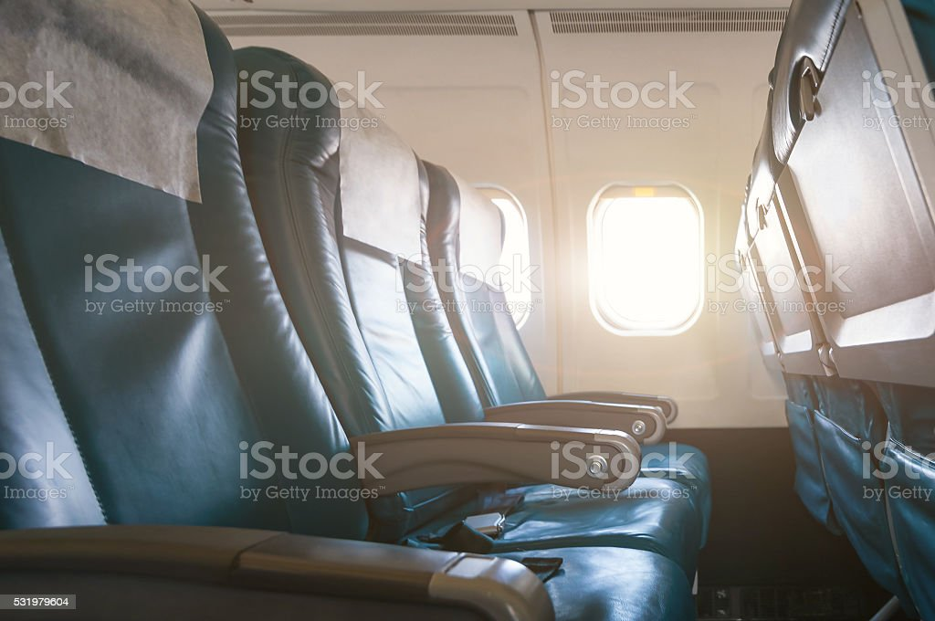 Empty aircraft seats and windows with sun light stock photo