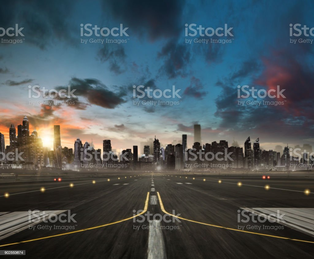 Empty airplane runway heading for the modern city with skyscrapers silhouettes. stock photo