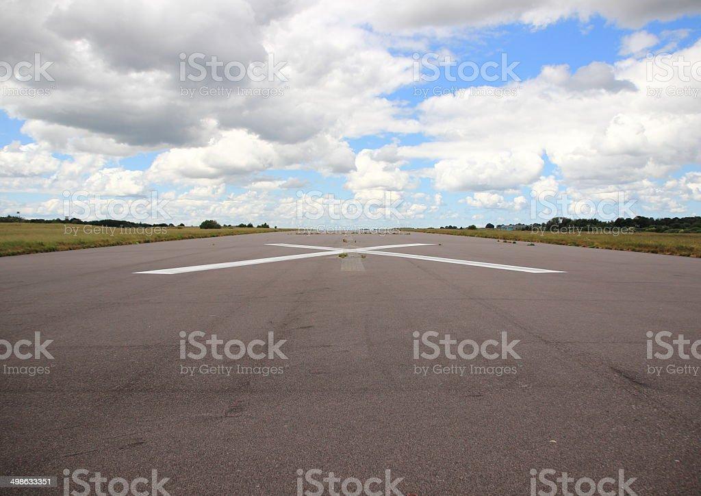 Empty airplane runway with white cross stock photo