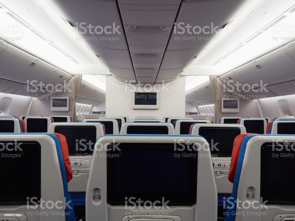 Empty airplane seats and blank screens stock photo
