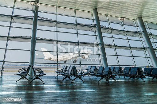 istock Empty airport departure lounge and airplane take off 1200778538